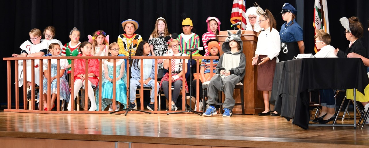 "Mickey Cox students performing on stage ""Goldilocks on Trial"""