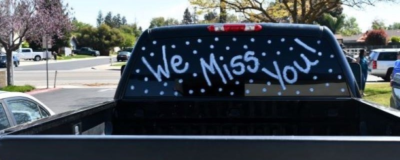 "Staff car with sign ""We Miss You"""