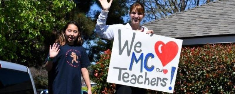 "Mickey Cox students holding a sign ""We love MC teachers"""