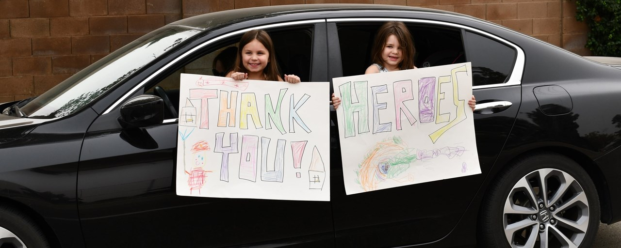 """two girls holding signs """"Thank you Heroes"""""""